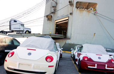 loading trucks onto a car carrier at the port