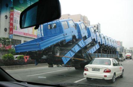 trucks hanging off the back of car hauler