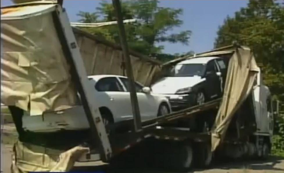Enclosed car carrier hits bridge